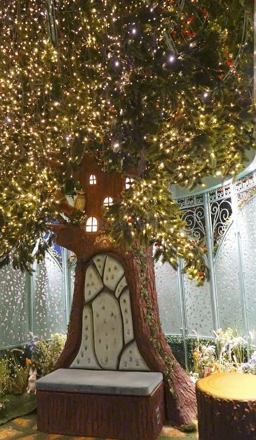 De plaats van de kerstman` s groet bij Capricieuze die tuin, in bloei wordt en met het fonkelen lichten wordt versierd behandeld  royalty-vrije stock foto
