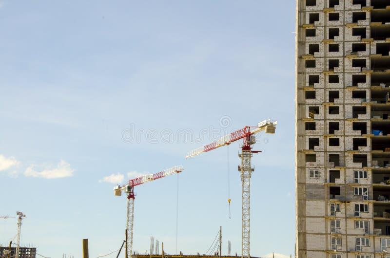 De plaats van de kraan en van de bouwconstructie tegen blauwe hemel stock afbeeldingen