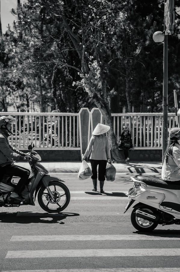 De plaatselijke bevolking draagt Vietnamese hoed kruisend straat met verkeer in DA Lat - Vietnam royalty-vrije stock fotografie