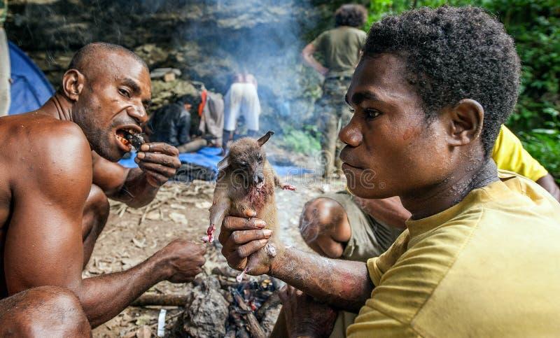 De plaatselijke bewoners papuan van het eiland Nieuw-Guinea hebben diner de gevangen vleerhond royalty-vrije stock fotografie
