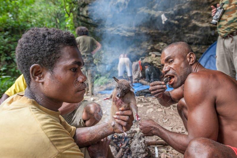 De plaatselijke bewoners van het eiland Nieuw-Guinea hebben diner de gevangen vliegvos royalty-vrije stock afbeelding