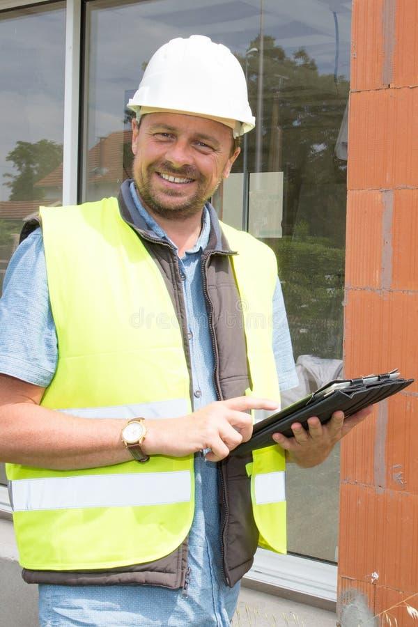De plaatsmanager op de bouw van een huis met helm en zijn veiligheid bekleden stock afbeeldingen
