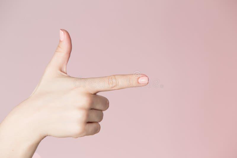 De plaatsthema van de schoonheidssalon Vrouwenhand met roze manicure die kanonteken tonen royalty-vrije stock foto