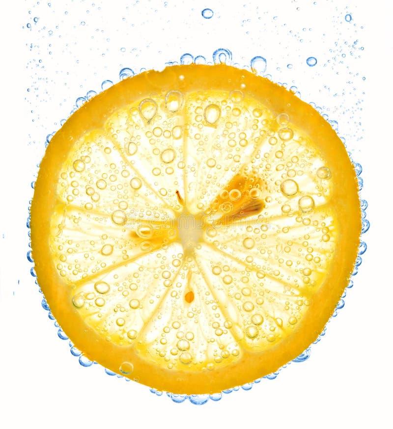 De plak van de citroen in duidelijk water stock foto's