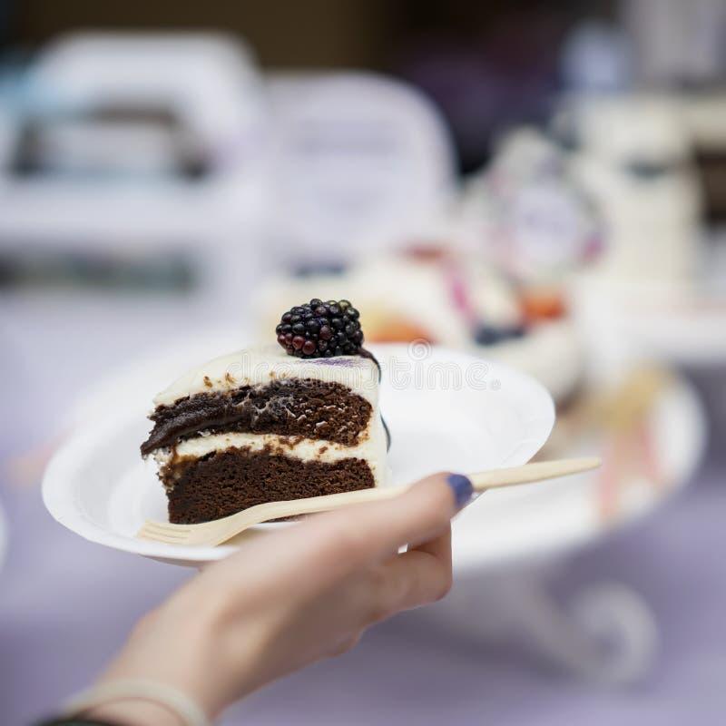 De plak van heerlijke chocoladecake met room en braambessen, plateert in hand, vers de zomerdessert, selectieve nadruk stock afbeelding