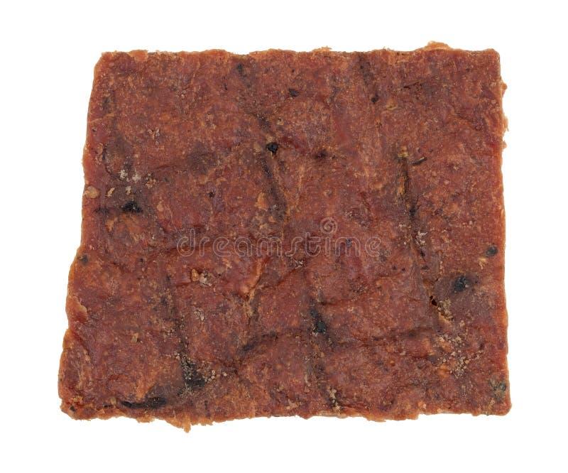 De plak van peppered rundvlees schokkerig op een witte achtergrond stock afbeeldingen