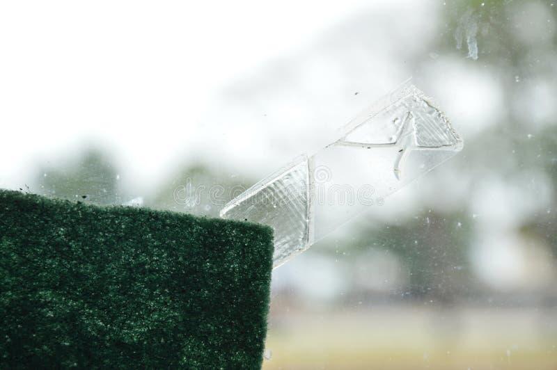 De plakbandvlek op het schild van het vensterglas en schrobt spons stock afbeeldingen