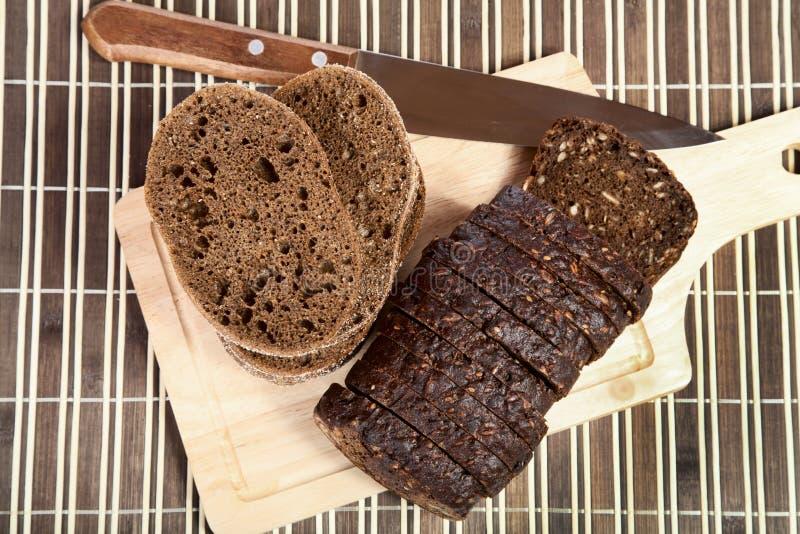 De plakken snijden zwart brood met mes royalty-vrije stock afbeelding