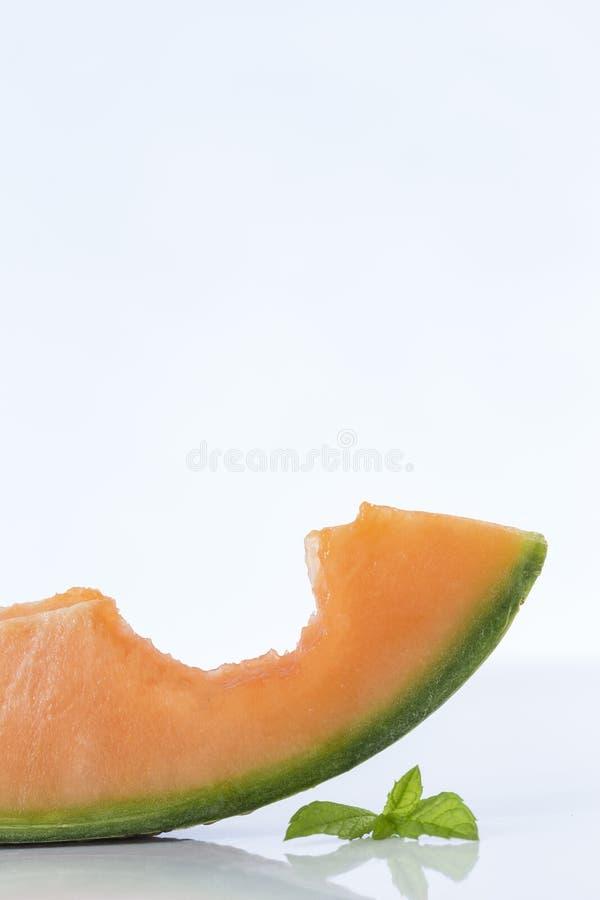 De plakken van de kantaloepmeloen met beet daarin royalty-vrije stock afbeeldingen