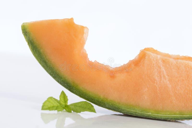 De plakken van de kantaloepmeloen met beet daarin stock afbeeldingen