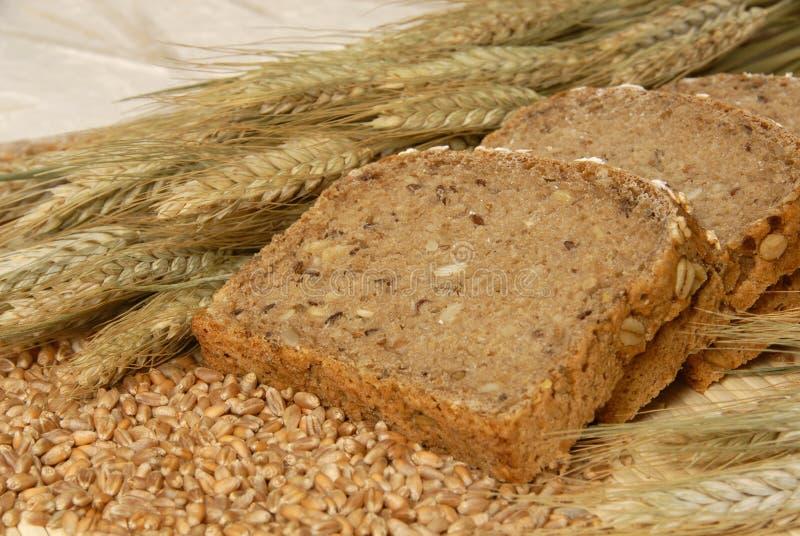 De plakken van het brood en natuurlijke graangewassen royalty-vrije stock afbeeldingen