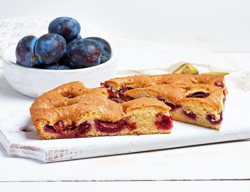de plakken van koekjespruim koeken op een witte houten raad en verse vruchten royalty-vrije stock foto