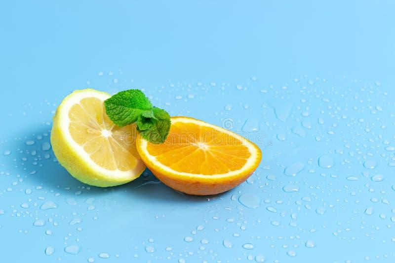 De plakken van sinaasappel en citroen met muntbladeren op een blauwe achtergrond met water daalt r stock foto