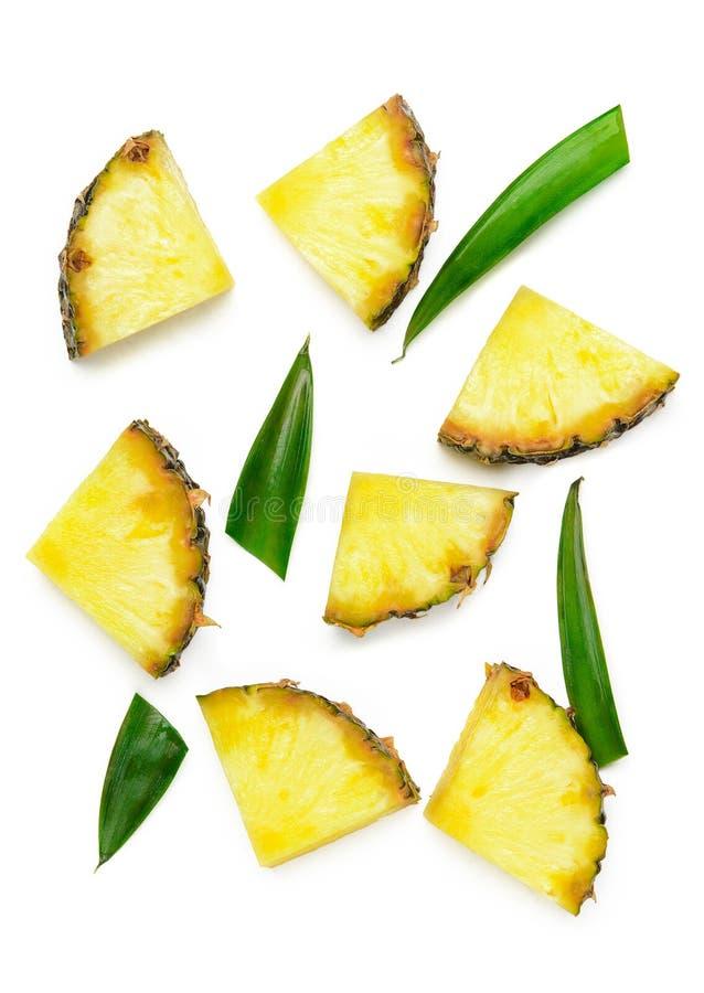 De plakken van unpeeled ananas en groene ananasbladeren op een witte achtergrond isoleren Sappige de zomer tropische dieet royalty-vrije stock afbeeldingen
