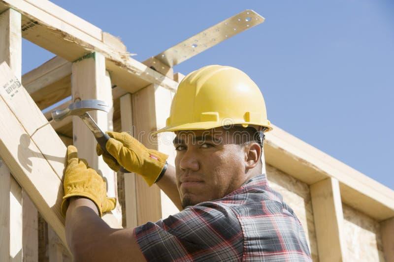 De Plank van bouwvakkerhammering nail the stock afbeelding