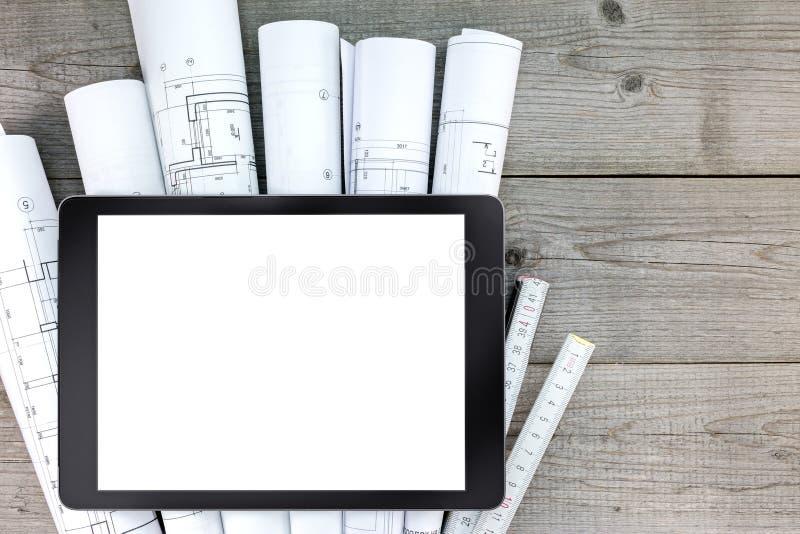 De plannen van de huisvernieuwing en lege tablet op houten achtergrond royalty-vrije stock fotografie