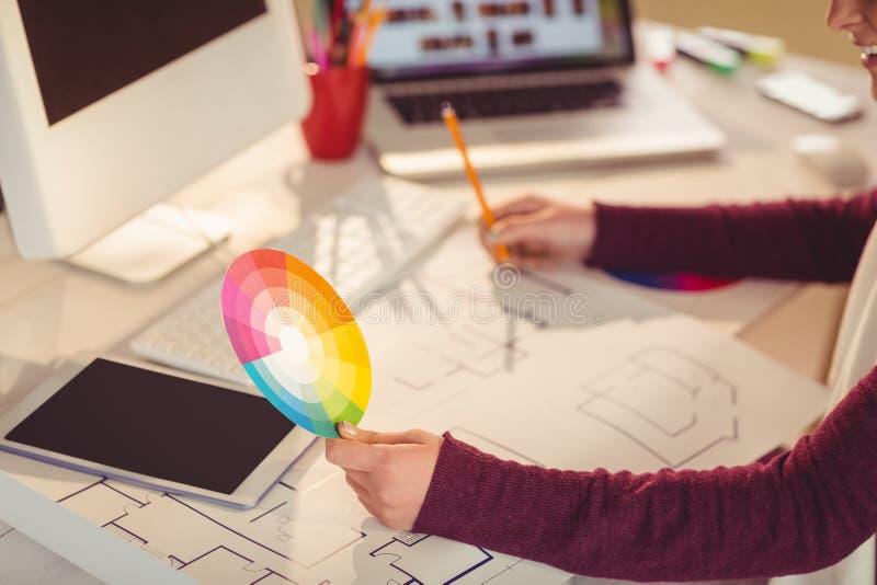 De plannen van de onderneemstertekening en houden een kleurenhorloge stock foto