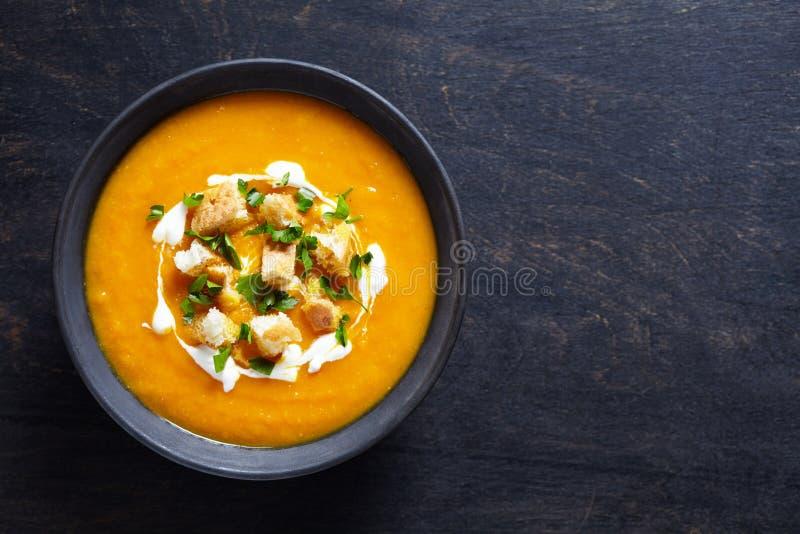 De plantaardige soep van de roompompoen met wortel en crackers Hoogste mening over een donkere creatieve achtergrond Gezonde diee stock foto