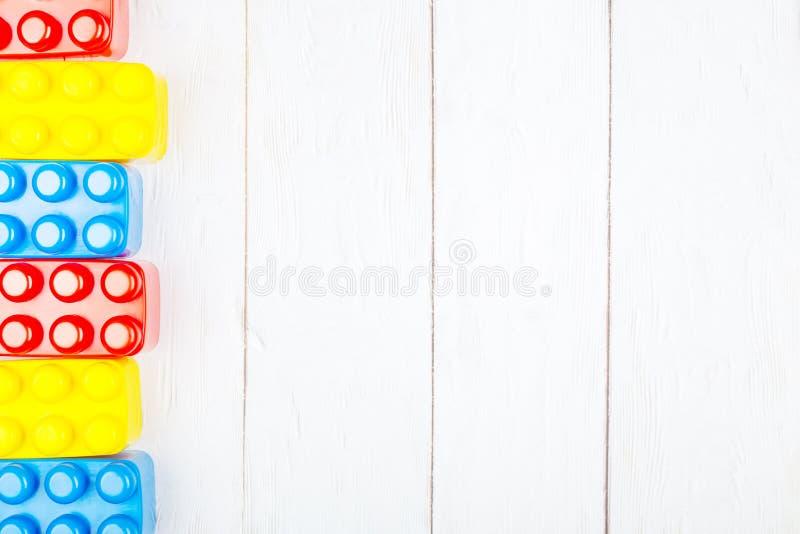 De plastic bouwstenen van kinderen Vlak leg op houten backgroun royalty-vrije stock foto's