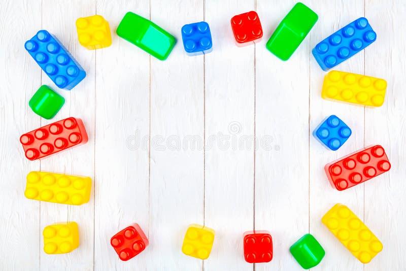 De plastic bouwstenen van kinderen Vlak leg op houten backgroun stock foto