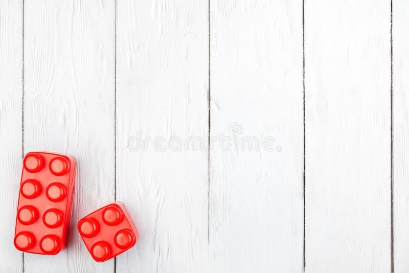 De plastic bouwstenen van kinderen Vlak leg op houten backgroun stock afbeeldingen