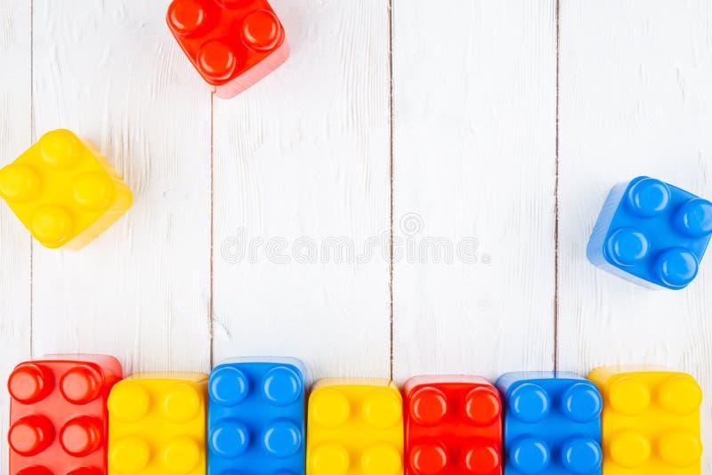 De plastic bouwstenen van kinderen Vlak leg op houten backgroun royalty-vrije stock afbeelding