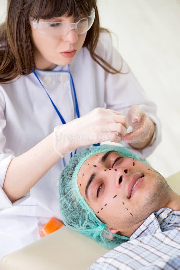 De plastic chirurg die voor verrichting op mensengezicht voorbereidingen treffen stock afbeeldingen