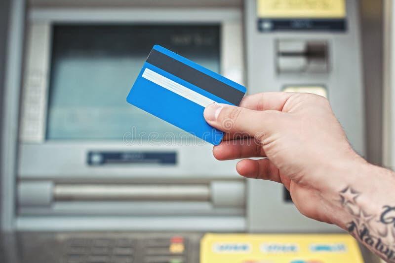 De plastic kaart van de handholding dichtbij ATM Betaalpasbetaling stock fotografie