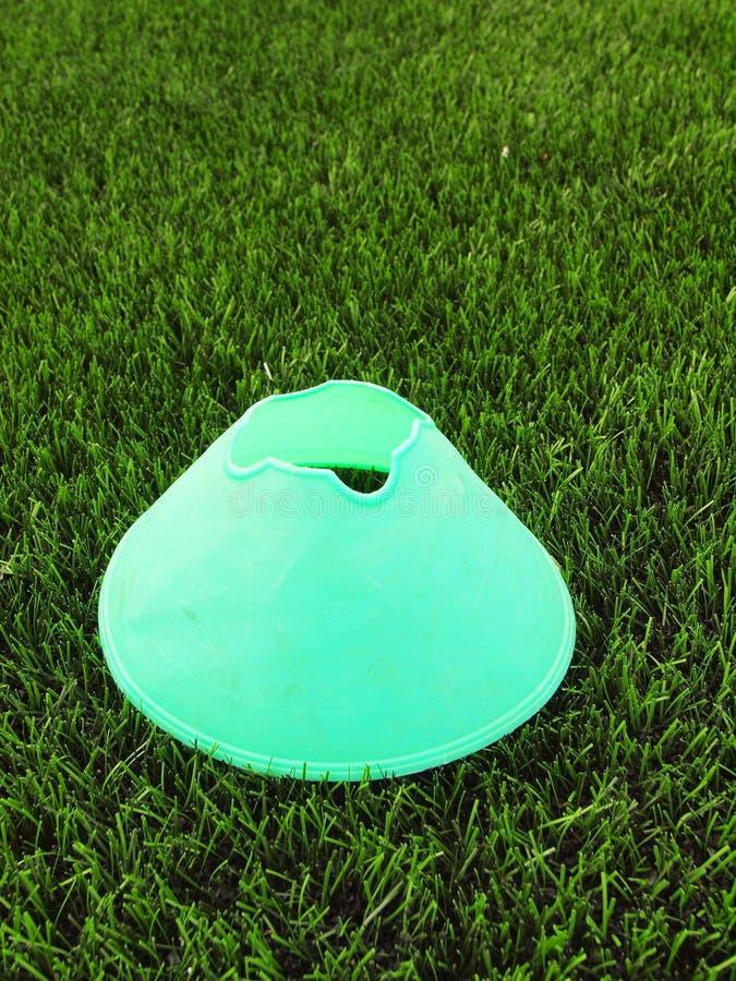 De plastic speelplaats van het voetbal groene gras met grinded zwart rubber in kern en heldergroene blauwe plastic kegel stock afbeelding