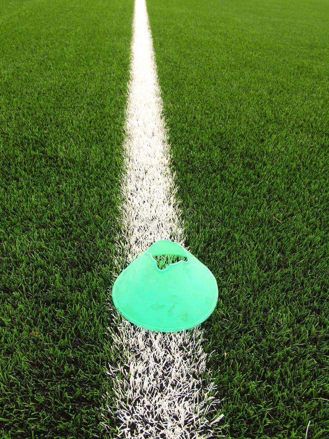 De plastic speelplaats van het voetbal groene gras met grinded zwart rubber in kern en heldergroene blauwe plastic kegel Witte li royalty-vrije stock foto's