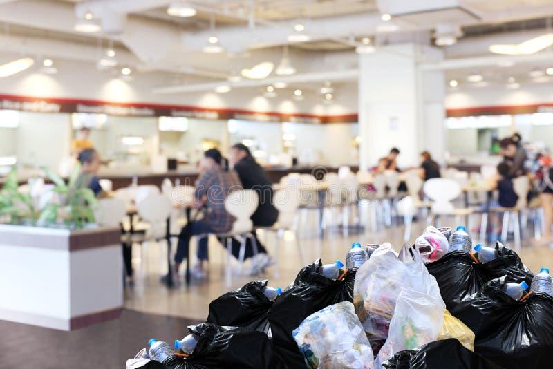 De plastic stapel van de bak volledige Partijen van de afvalvuilniszak zwarte van troep bij voor van de het hofwandelgalerij van  royalty-vrije stock afbeelding