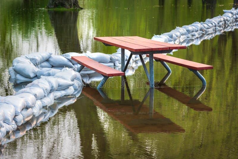 De plastic zandzakken van de vloedbescherming die in een tijdelijke muur rond de picknicklijst worden gestapeld om park tegen vlo stock foto