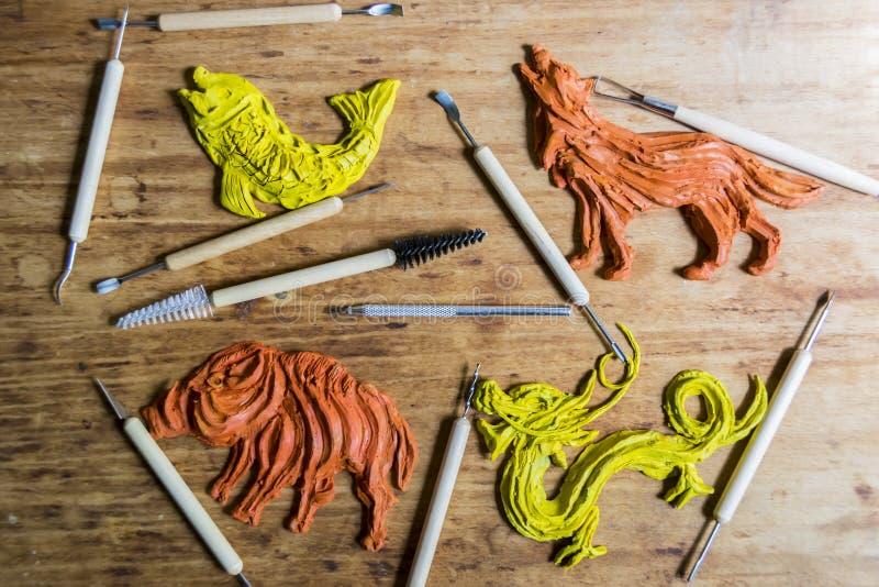 De plasticine van de beeldjeklei in een workshop met hulpmiddelen op houten bedelaars stock afbeelding