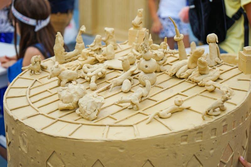 De plasticinebeeldjes van kinderen bij de hoofdklasse bij de modellering van plasticine royalty-vrije stock afbeelding