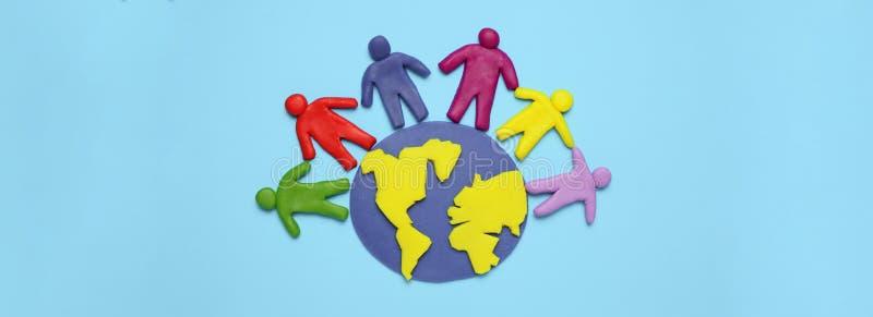 De plasticinebeeldjes van mensen van verschillende rassen zijn op aarde Een verscheidenheid van interactie, mededeling en globali stock foto