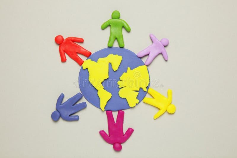De plasticinebeeldjes van mensen van verschillende rassen zijn op aarde Een verscheidenheid van interactie, mededeling en globali stock afbeeldingen