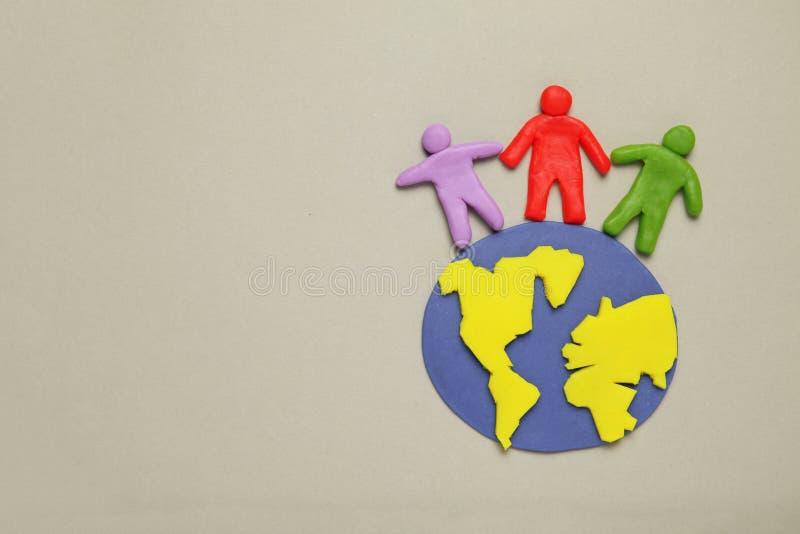 De plasticinebeeldjes van mensen van verschillende rassen zijn op aarde Een verscheidenheid van interactie, mededeling en globali stock fotografie