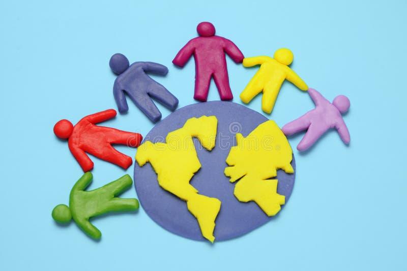 De plasticinebeeldjes van mensen van verschillende rassen zijn op aarde Een verscheidenheid van interactie, mededeling en globali royalty-vrije stock afbeelding