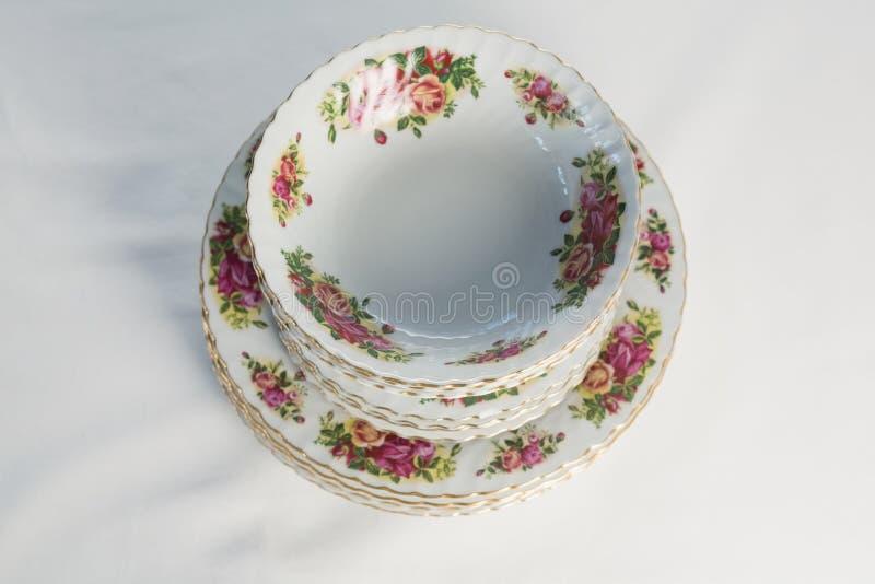 De platen en de kom met bloemenontwerp plaatsen elegant op een lijst stock foto's