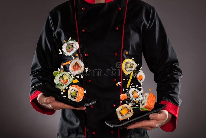 De platen van de chef-kokholding met het vliegen sushistukken royalty-vrije stock fotografie