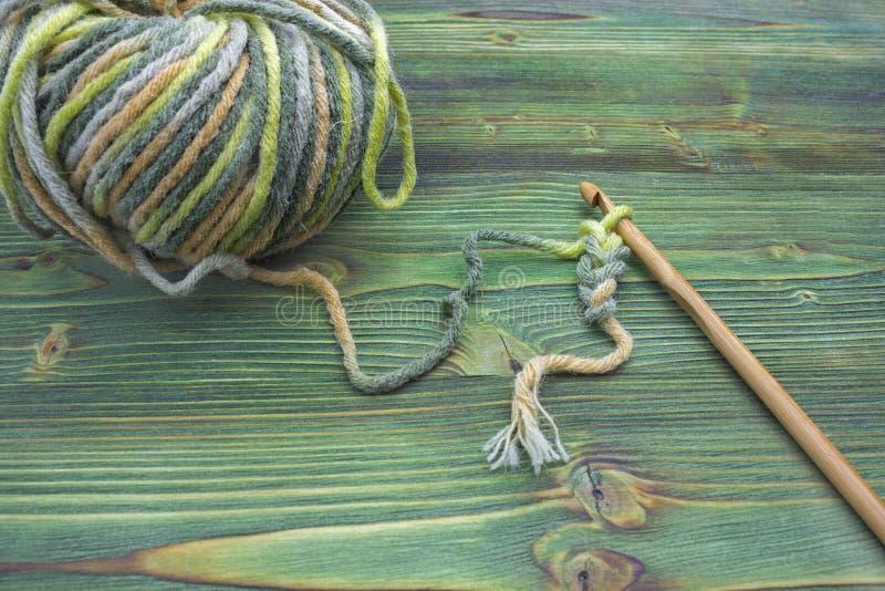 De plattelander haakt draad en een bamboehaak De warme roze bal van het de wintergaren voor het breien en haakt op de houten lijs royalty-vrije stock afbeelding