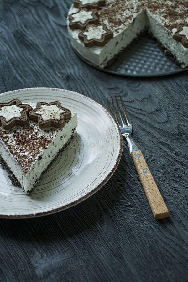 De plattelandshuisjekaastaart zonder gebakken kaastaart is verfraaid met koekjes en geraspte zwarte chocolade op een donkere hout royalty-vrije stock foto