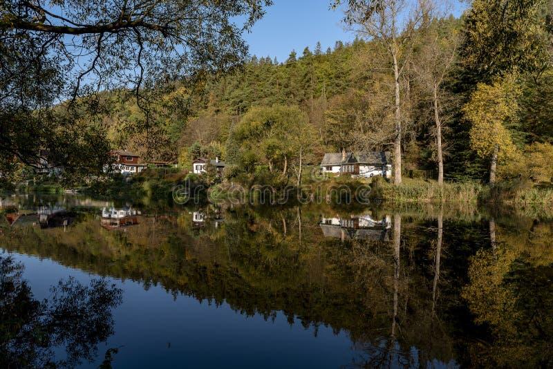 De plattelandshuisjes en de plattelandshuisjes onder de bomen overdachten de oppervlakte van de rivier Sazava royalty-vrije stock afbeelding