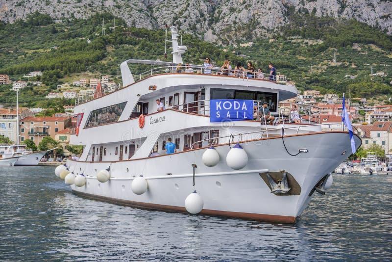 De plezierboot met vrolijke toeristen gaat de haven van Makarska, Kroatië in stock fotografie