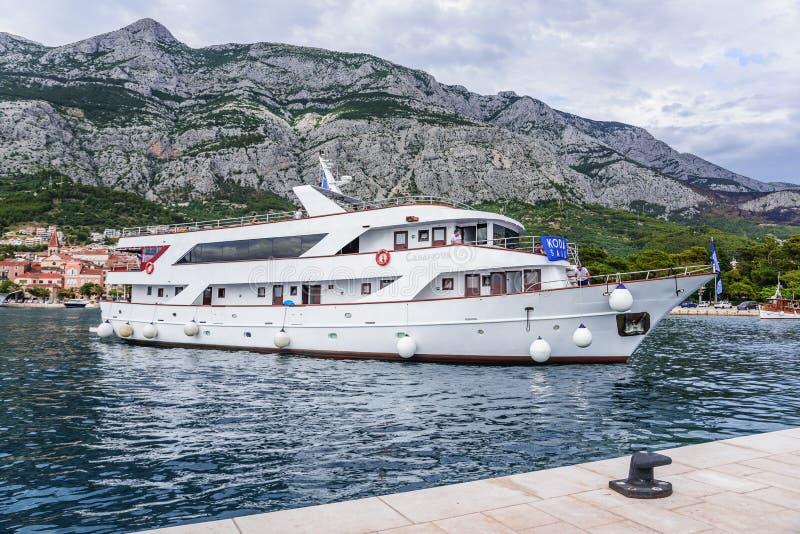 De plezierboot met vrolijke toeristen gaat de haven van Makarska, Kroatië in stock foto's