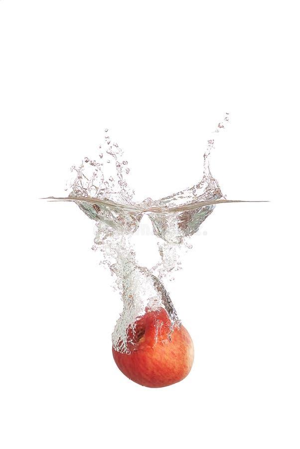 De plons van de appel in water stock fotografie