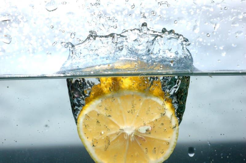 De plons van de citroen in water stock fotografie