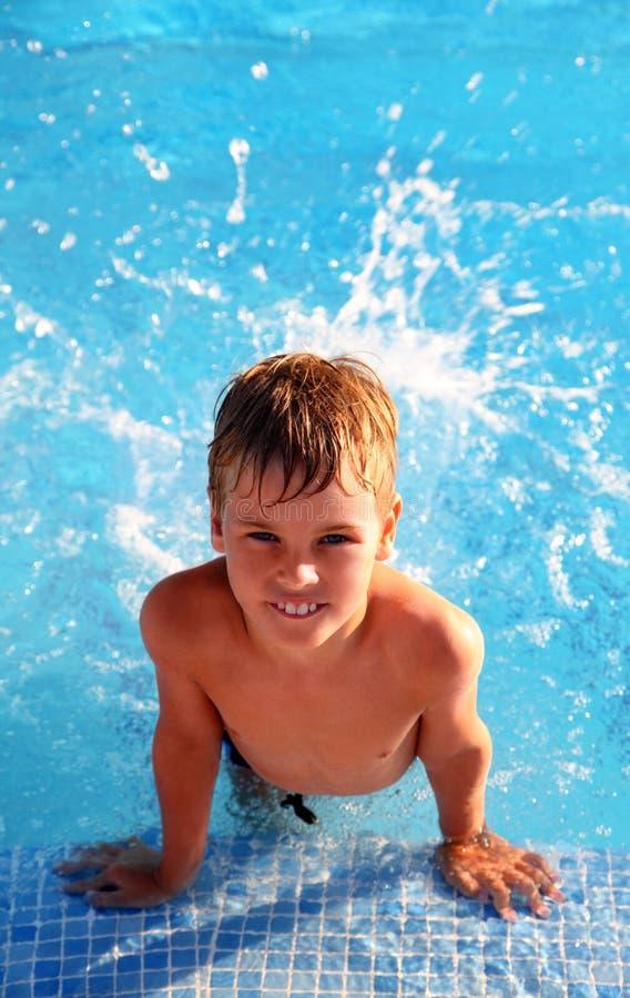 De plons van de jongen rond in water in zwembad stock afbeelding