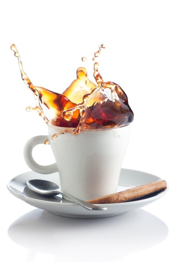 De plons van de koffie in een kop stock foto
