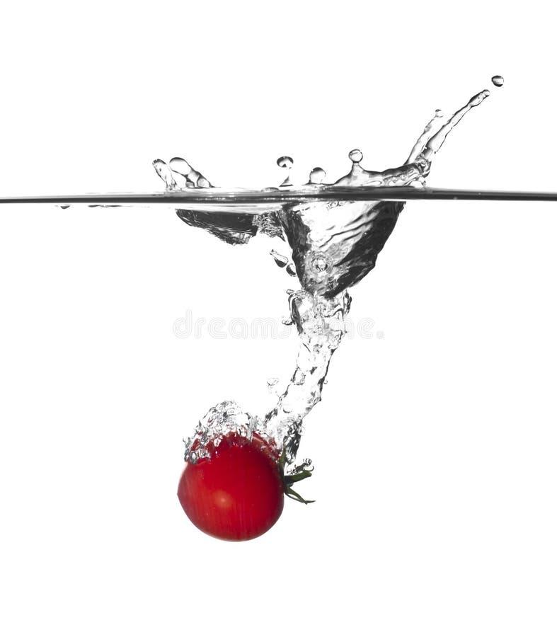 De plons van de tomaat in water stock afbeelding